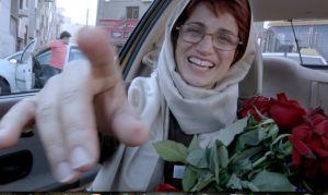 """Nasrin Sotoudeh i baksätet på en bil med en bukett röda rosor. Bilden är från Jafar Panahi's film """"Taxi Téhéran""""."""