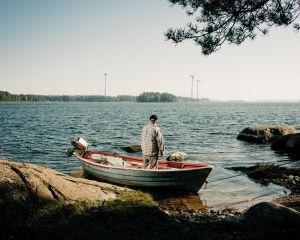 Jarmo Mustonen seisoo veneessään ja katsoo merelle kalastusmökillään Kotkassa.