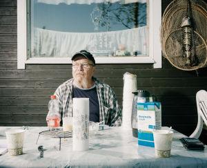 Jarmo Mustonen istuu pihallaan pöydän ääressä, jossa on kahvia ja kahvimukeja.