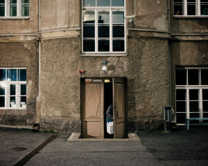 Kuvassa näkyy luonnontieteellisen museon sisäpihalla rakosellaan auki oleva ovi. Ovensuussa näkyy käsivarsi, joka pitelee kylmälaukkua.