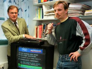 Televisiovastaanottimen takana vasemmalla seisoo Jorma Lampinen, teksti-tv:n päällikkö ja oikealla Tapio Vuorinen (2000).