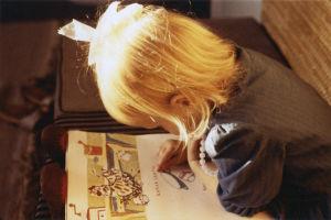 Kirjailija Johanna Sinisalo 3-vuotiaana yläviistosta kuvattuna kumartuneena kirjan päälle lukemaan. Tyttö seuraa sormellaan tekstiä.