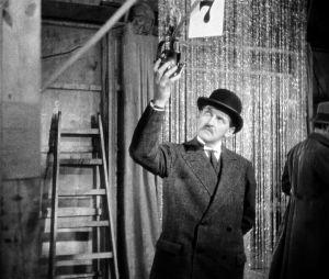 Rikosylikomisario (Ernst Stahl-Nachbaur) tarkastelee mikrofonia elokuvastudiolla.