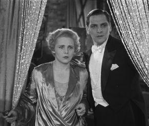 Asetta pitelevä nainen ja frakkipukuinen mies katsovat hämmästyneinä. Kuva elokuvasta Laukaus äänifilmistudiossa