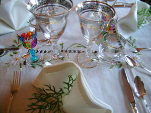 Kaunis, arvokkaannäköinen pöytäkattaus pikareineen ja kankaisine lautasliinoineen