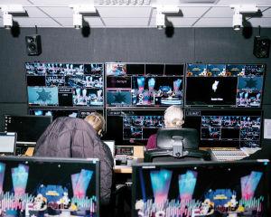 Kuva ohjaamosta, jossa kaksi naista katsoo televisioseinää.
