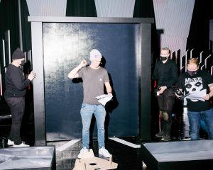Pipopäinen mies seisoo lavasteseinän edessä paperinippu kädessään.
