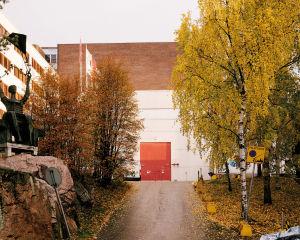 Syksyinen maisema, jonka keskellä näkyvät isot teollisuushallin ovet.