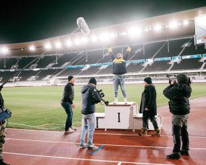Henkilö tuulettaa olympiastadionilla samalla, kun kuvaajat kuvaavat.