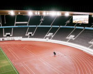 Yksi ihminen noukkii kymmeniä maahan levittäytyneitä palloja Olympiastadionilla.