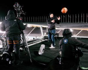 Toppatakkiin pukeutunut mies ottaa koripallon ilmasta Olympiastadionin katolla.