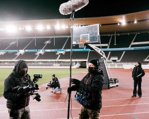 Kaksi kuvaajaa, yksi äänittäjä ja yksi käsikirjoittaja seisoo maantasalla Olympiastadionilla.