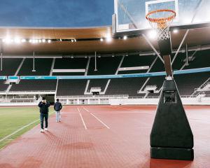Mies pitää päätään käsissään Olympiastadionilla seisovan koripallokorin vieressä.