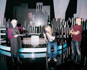 Nainen osoittaa lavalle, kaksi miestä katsoo studiolavasteissa.