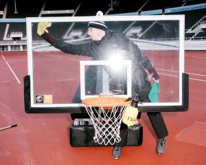 Henkilö putsaa koripallokoria rätillä ja pesuaineella Olympiastadionilla.