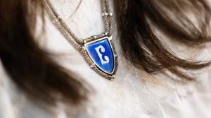 Närbild på ett luciasmycke som bärs av en flicka med mörkt hår