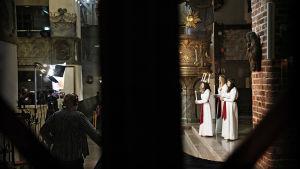 Bild tagen på långt håll. Luciatrio står framför ett altare, i bilden syns också män och tv-kamera.