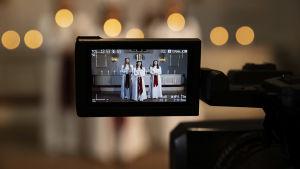 Närbild av en tv-kamera, på skärmen syns en luciatrio