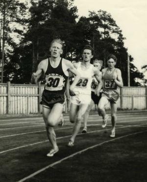 Miehet juoksevat kilpaa juoksuradalla.
