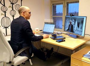 En man sitter på ett kontor framför ett skrivbord. Man ser hans datorskärm där han själv är i bild.