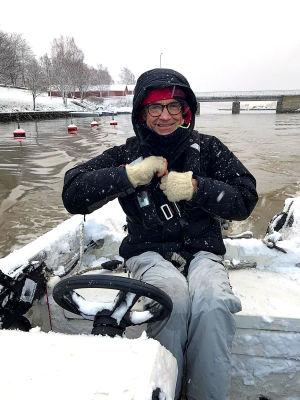 Fritjof sitter i en snöig öppen båt på väg ut från hamnen. Det snöar ute och man ser snöflingorna yra iluften. Han har svart jacka med huva uppdragen över huvudet.
