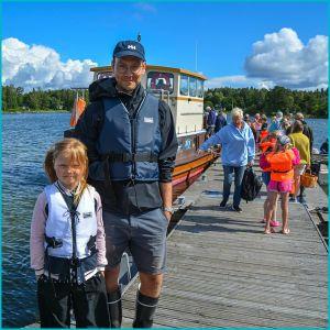 En man och en flicka står på en brygga, i bakgrunden syns människor som kommer ut från en båt