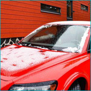 En röd bil täckt av snö