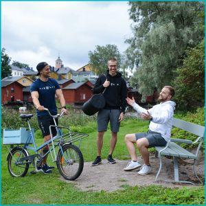 Tre glada män som står ute i naturen