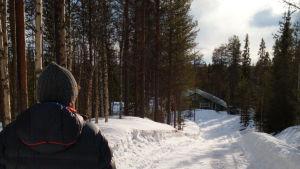 Mies katsoo eteenpäin kohti lumista tietä.