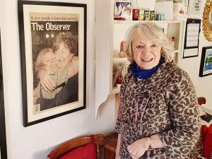 Jane Morrice i sitt kök. På planschen tidningen The Observers förstasida 22 maj 1998, den dag nordirländarna röstade för att godkänna långfredagsavtalet. På tidningsbilden ser man en lycklig Jane krama om en annan kvinna.