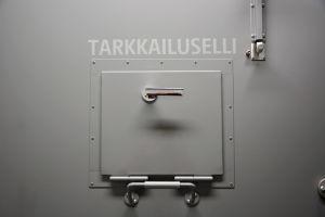 en grå dörr till en fängelsecell med lucka som är fast