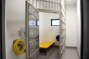 en fängelsecell med traditionellt galler som väggar och en enkel gul säng