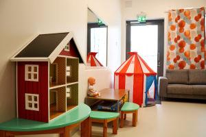 ett rum med ett dockhus, en docka, en spegel, ett litet cirkustält, en soffa och gardiner med orangeröda detaljer på