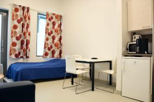 ett rum med ett bord och några stolar, ett fönster med gardiner med orangeröda detaljer, en säng med ett blått överkast på, ett litet kylskåp, en mikro, kaffe- och vattenkokare