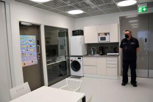 ett person står i ett kök med köksutrustning och tvättmaskin, bord och stolar och en dörr till ett övervakningskontor i ett fängelse