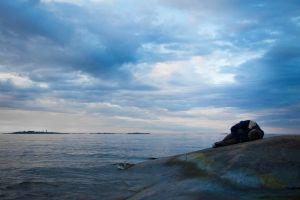 Mies makaa sikiöasennossa kalliolla meren rannalla.