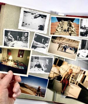 Avattu valokuva-albumin aukeama, käsi pitelee yhtä valokuvaa.