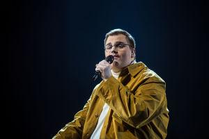 Aksel laulaa mikrofoniin päällään sinapinkeltainen kauluspaita, jonka alla on valkoinen paita. Hän katsoo sivuttain kameraan.
