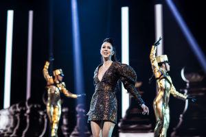 Laura laulaa lavalla kultaisessa glitter-mekossa, taustalla kaksi kultaisiin haalareihin ja hattuihin pukeutunutta tanssijaa.