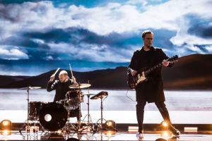 Haloo Helsingin Leo Hakanen soittaa kitaraa ja Jukka Soldan soittaa rumpuja lavalla. Taustascreenillä aavikkoa ja sininen pilvinen taivas.