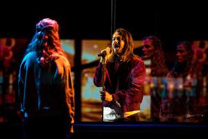 Oskr laulaa lavalla standissa olevaan mikrofoniin pitäen standista kiinni, hänen edessään seisoo nainen selin kameraan. Naisen kasvot heijastuvat lasista Oskrin takaa.