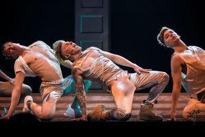 Antti Tuisku ja kaksi tanssijaa lavalla toinen polvi ja käsi maassa, ylävartalo ja lantio käännettynä ylöspäin. Antti laulaa tunteella.
