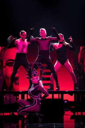 Antti Tuisku seisoo lavarakennelman päällä kahden tanssijan kanssa, kädet sivuille kohti ilmaa nostettuna ja suu laulusta auki. Erika Vikman istuu edessä puolikyykyssä ja katsoo vaativasti kameraan valtava pääkoriste päässään.