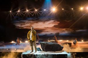 Aksel laulaa mikrofoniin lavalla, jolla on isoja kiviä ja valkoista savua. Taustalla neljä tanssijaa kyykyssä.