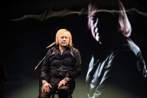 Mustaan paitaan pukeutunut Danny istuu lavalla jakkaralla mikkistandin edessä. Taustascreenillä Danny itse.