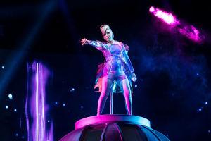 Pandora laulaa lavalla hopeisessa avaruushenkisessä asussa, toinen käsi ojennettuna eteen.