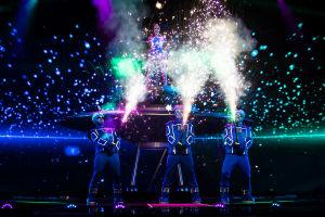 Teflon Brothers lavalla avaruusolioasuissa ja aivoja muistuttavissa päähineissä, kädessä tähtisadetta ampuvat kepit. Taustalla lentävä lautanen jolla Pandora seisoo.