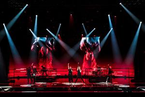 Blind Channel -yhtye lavalla punaisen screenin edessä keskisormet pystyssä. Taustacreenillä laulajat roikkuvat ylösalaisin.