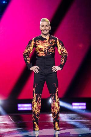 UMK-juontaja Antti Tuisku seisoo lavalla kädet lanteilla pukeutuneena mustaan asuun jossa on liekkejä.