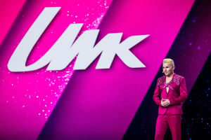 Magentan väriseen pukuun ja glittervaljaisiin pukeutunut Antti Tuisku seisoo lavallla screenin edessä, jossa lukee UMK.
